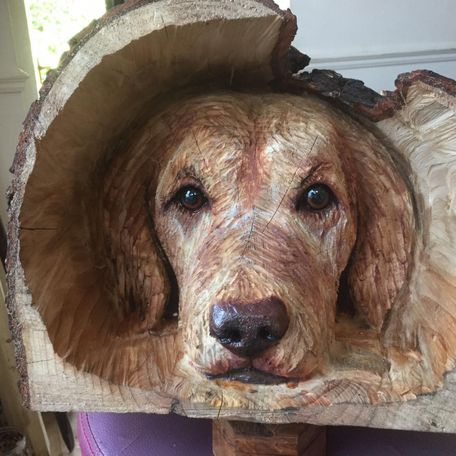 Dog head, carved into a log, with painted high lights